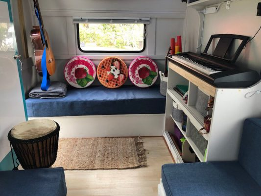 Little Musical Caravan inside front view with instrument cabinet on the right, pink and orange cushions and guitar hanging on left wall